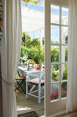 A view through open French windows of a table laid on the terrace