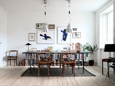 Black dining table with Thonet chairs in front of half-height bookcase and lithographs on white wall