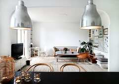 A view over a black dining table into a living room with a shell chair, a coffee table and a sofa