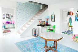 An octagonal wooden table on a blue-and-white rug in an anteroom with a white wooden floor and a staircase in background