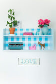 Houseplant, a bouquet of roses, wooden boxes, and figures on a wall shelf with a blue and white checkered back wall