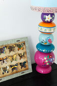 Table lamp with a decorative lamp base next to a showcase with butterflies