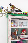 An old glass cabinet filled with family photos, animal figures and books