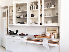 A fitted kitchen with glass cabinets and white fronts