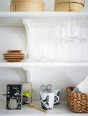 Organized shelf with glasses, tea, cups, and other kitchen accessories