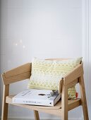 A patterned cushion and a recipe book on modern chair