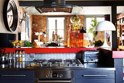 A blue kitchen with a gas cooker and a stainless steel worktop in front of a hatch