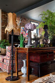 Leather suitcase under an antique console table and floor lamp in the living room with a brick wall