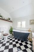 Freistehende Badewanne aus genietetem Metall im klassischen Bad