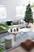 Pale sofa and round tables on grey rug next to decorated Christmas tree