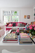 View past books on coffee table to hot-pink wicker sofa with brightly coloured scatter cushions