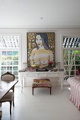 White table with drawers and upholstered stool below painting on wall between lattice windows