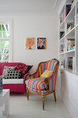 Antique armchair with striped cover and pink-painted wicker sofa next to bookcase