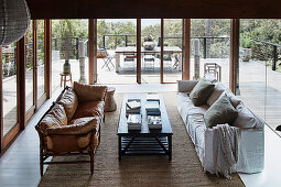 Leather sofa and slipcover sofa around coffee table in lounge with all-round glazing
