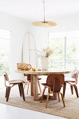 Round wooden table with classic chairs in a bright dining area, surfboard in the background