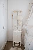 Bedside table below lamp mounted on old window shutter in bedroom