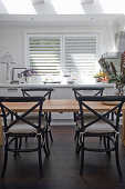 Black bistro chairs at wooden table in bright kitchen-dining room
