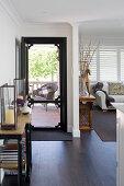 Open front door in classic living room with dark floor