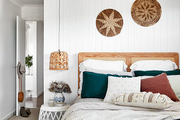 Double bed with wooden headboard against white wooden wall