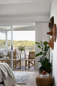 Ethnic wall decorations and houseplant in bedroom with balcony