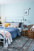 White bed in pale blue bedroom