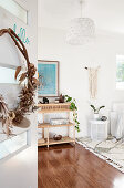 Wreath of dried plants on door and rattan shelves in white living room