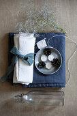 Weißer Stoff mit blauem Band, Teelichter, Zapfen, Garn, Blütenzweig und Bügelflasche