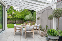 Dining table and rattan chairs on terrace with pergola