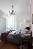 Double bed against pink bedroom wall and ensuite bathroom behind wall with patterned wallpaper