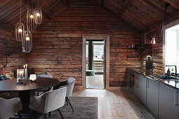 Cosy and elegant kitchen-dining room in rustic wooden cabin
