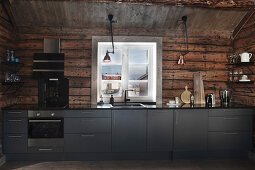 Modern fitted kitchen with grey fronts in rustic wooden cabin