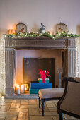 Lit candles and wrapped gifts in disused fireplace with Christmas decorations on mantelpiece