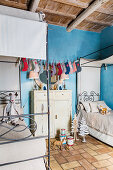 Festively decorated siblings' bedroom with blue wall in renovated farmhouse