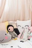 Stofftiere und Kissen unter rosafarbenem Baldachin