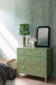 Green chest of drawers against wall with woodland motif in bedroom