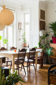 Spoke-back chairs around dining table and houseplants in interior