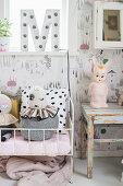 Dekobuchstabe am Fenster überm Puppenbett im Kinderzimmer in Grau