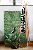 Urban Jungle accessories: green artwork and pouffe, bird ornament and cage and wooden coat stand