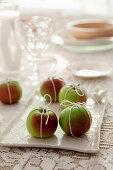 Äpfel mit Bändern umwickelt als weihnachtliche Tischdekoration