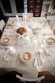 Blick von Oben auf weihnachtlich gedeckten Tisch in Weiß mit Spitzendecke und Teelichtern