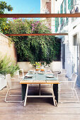 Set dining table in summery wooden terrace adjoining house