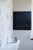 Dandelion-patterned wallpaper and chalkboard in corner