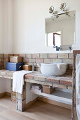 Masonry washstand and marble sink in rustic bathroom of Tuscan country house