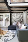 Graues Übereck-Ledersofa im Wohnbereich unter Zwischengeschoss in einer Loft-Wohnung