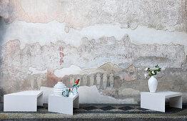 Vasen und handbemalte Porzellan-Vögel auf weißen Designertischen vor künstlerisch gestalteter Wand