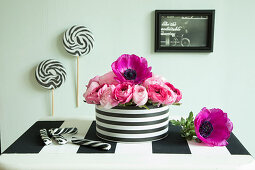 Pink flowers in black-and-white striped tin