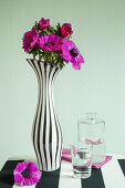 Bouquet of pink flowers in black-and-white striped vase