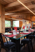 Festively set table with black upholstered chairs in dining area of chalet