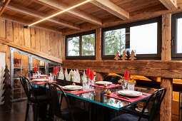 Festively set table and black, upholstered chairs in dining area of chalet