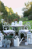 White, shabby-chic seating area on terrace with autumnal decorations